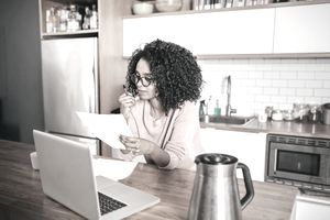 Woman reviewing papers next to a laptop in her kitchen.