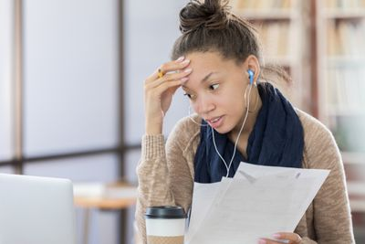 A worried college student has one hand on her forehead while holding papers and looking at a laptop searching for a job