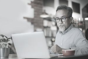 older person sitting at computer doing work with red coffee cup in front of him