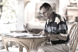 Retired man calculating his taxes at a small home table
