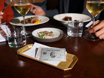 A Platinum Card from American Express rests on a restaurant dining table.