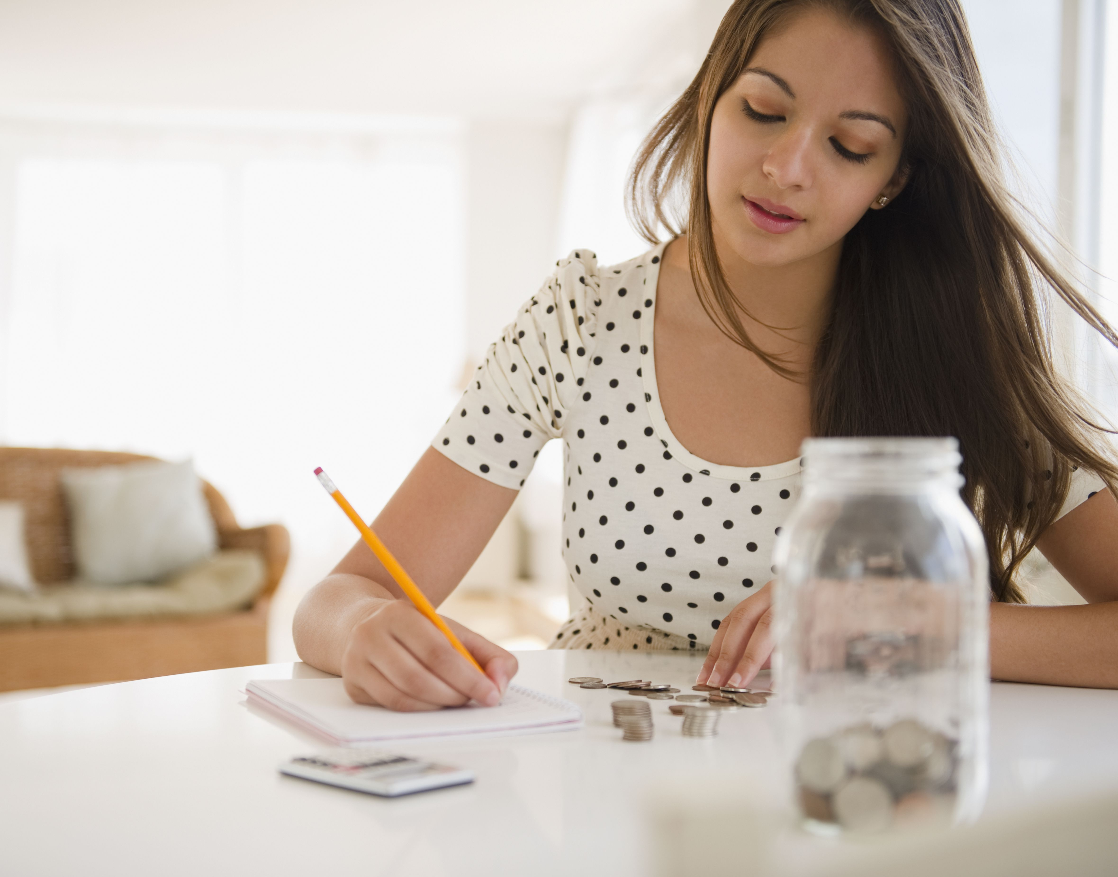 woman counting coins and saving change in a jar