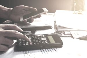 Man using smart phone and calculator to determine the amounts of his chapter 13 payment.