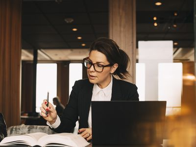 Woman in front of laptop at desk studying pricing