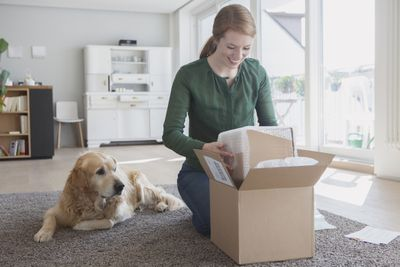 Woman opening a package with her dog watching