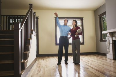 Real estate agent and buyer explore a propert on the market.