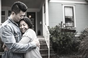 Asian Couple Hugs in Front of Their House