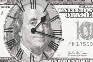 Clock on one hundred dollar bill representing the time value of money.