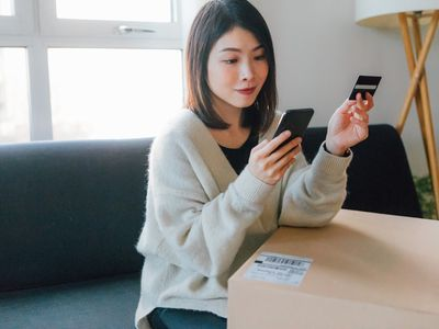 A woman uses a prepaid debit card and her smartphone to shop online