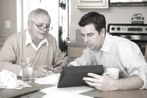A father and son go over bills in front of a tablet
