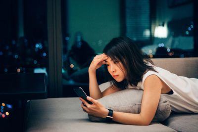Young woman working late and checking work email on mobile at home