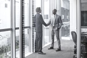 Two businessmen in suits shaking hands in an office