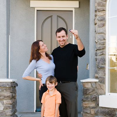 New Home Buyers with young child in front of door