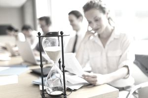 woman looking at paperwork next to hourglass