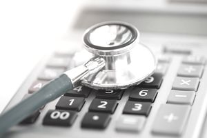 Stethoscope resting on a calculator, representing the costs of Medicare Part B.