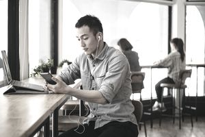 Man with laptop uses earbuds and cellphone in cafe