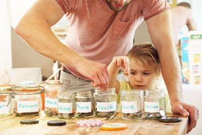 Young girl and father putting money into savings jars