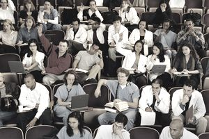 Medical Students, Some in White Coats and Scrubs, Listening and Participating in a Class Lecture in Tiered Seats