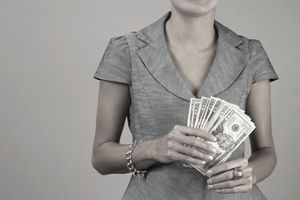 a woman holding a wad of 20 dollar bills