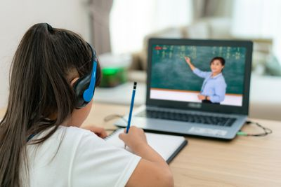 Student videoconferencing with teacher on computer in living room