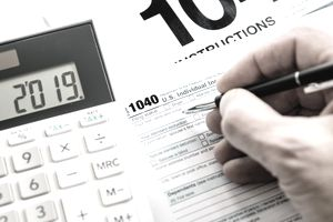 Hand Holding Pen Filling Out Form 1040 With Calculator Nearby