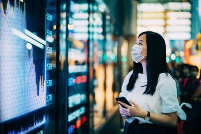 Businesswoman with protective face mask checking financial trading data on smartphone by the stock exchange market display screen board