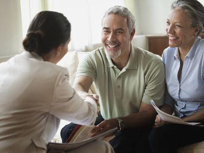 Saleswoman shaking hands with clients in living room