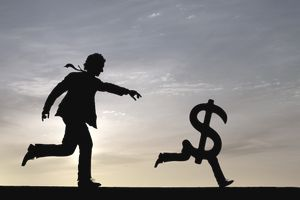 A man chases a dollar sign with legs along a surface as the sun sets in the background