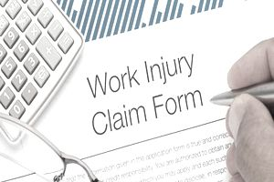 Employee with pen in hand filling out work injury claim form with calculator and glasses