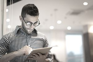 person with glasses on iPad in the office