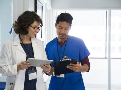 A doctor and a nurse review information on a tablet device.