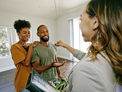 Female real estate agent handing house keys to a young couple