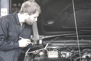 person in jumpsuit with ipad in hand, fixing a car