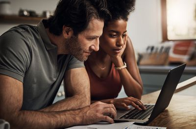 A young couple reviews their investments on a laptop.