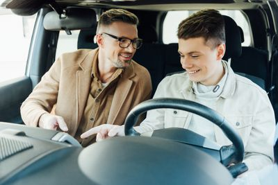 A parent and teen look at a new car.
