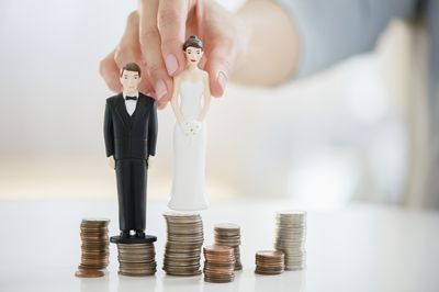 Bride and groom as game pieces standing on top of coin stacks