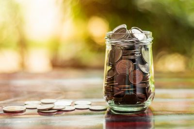 Close-Up Of Coins In Jar On Table