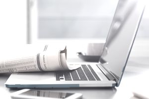 Business section of newspaper laying on a laptop keyboard
