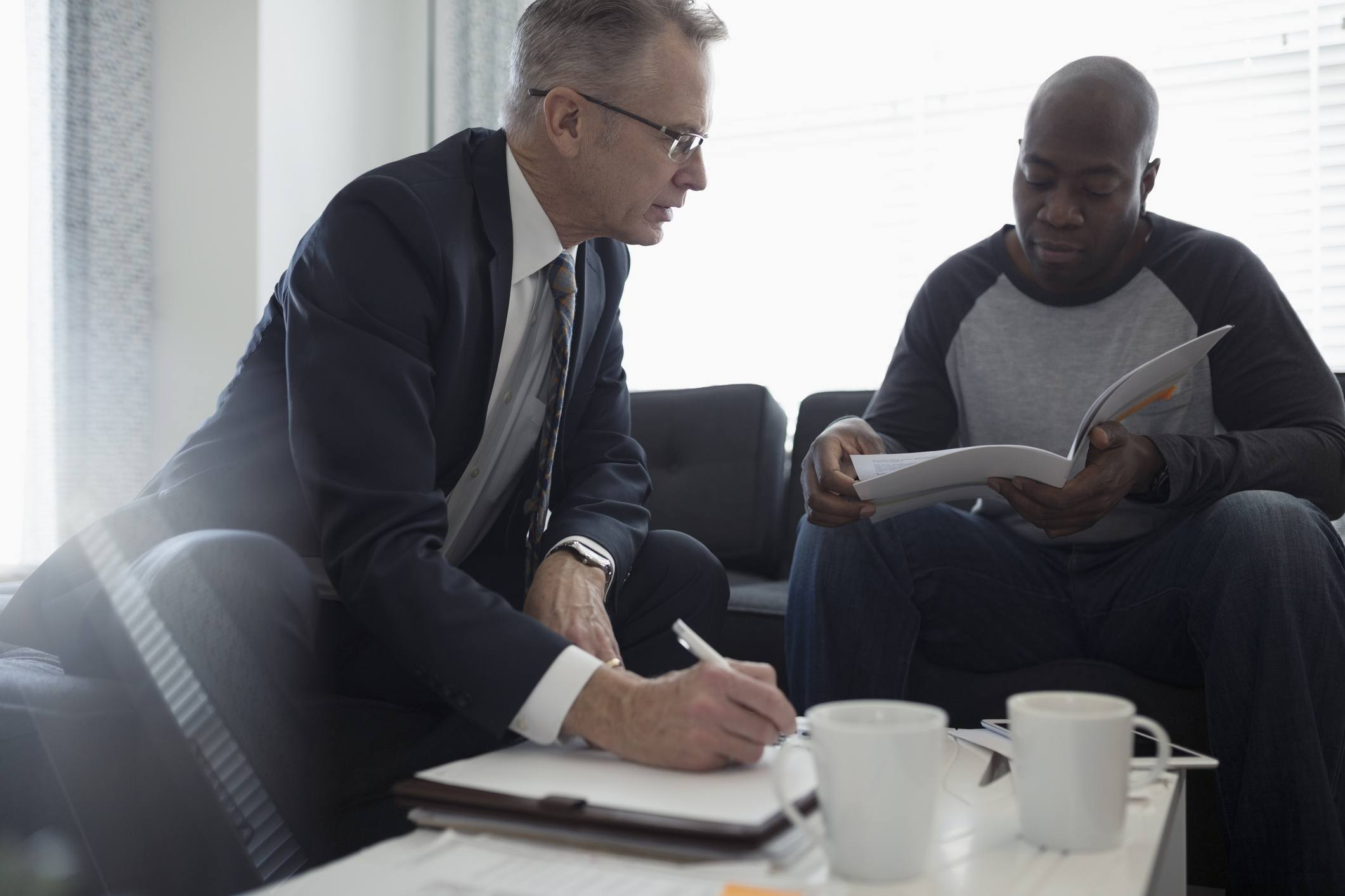 Financial advisor discussing paperwork with man in living room