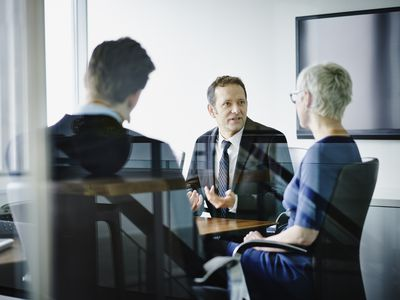 Attorney, man, and woman talking at a conference room table