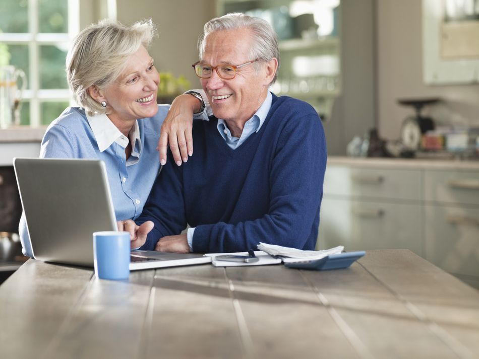 Elderly man and woman sitting at a kitchen table using a laptop