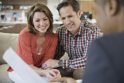 Couple smiling as the review paperwork at home from a professional