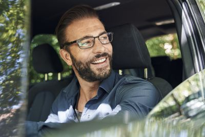 A smiling man with glasses sits in driver's seat