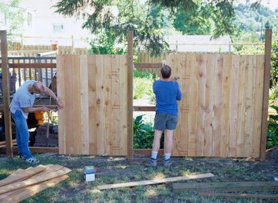 Two carpenters building a wooden fence between residential properties