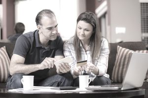 Latin descent couple paying monthly bills at home.