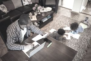 Father working at home and watching kids on the floor in the living room.