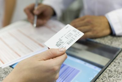 Patient handing health insurance card across counter at a doctor's office