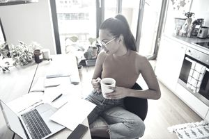 Young woman seated at home desk with laptop, doing taxes