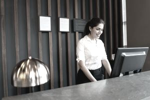 Latin American female hotel employee with computer