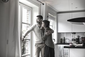 Pensive man embracing young woman looking out of window in kitchen.